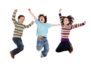 Three happy children jumping at once on a white background